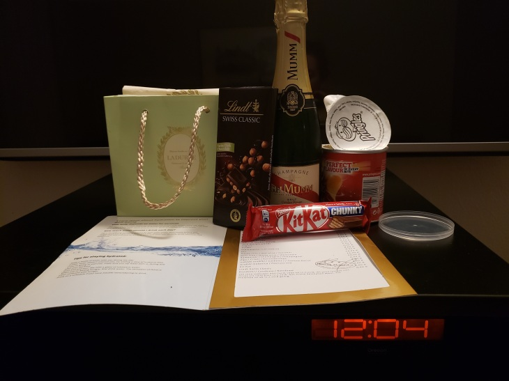 the Laduree sac, a Lindt chocolate bar, a half-bottle of Mumm's champagne, opened bottle of small Pringles, chunky Kit Kat bar all laid out of the mini bar fridge with a digital clock showing the time: 4 minutes past midnight