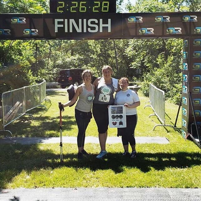 My teammates and me under the finish chute at the Hudson Crossings Triathlon. We are wearing our Wellnest Studio shirts, and carrying the transition towel that was given to us instead of a medal. I am holding my hiking poles.