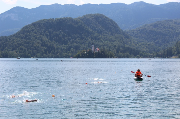 view of the lake with a few swim caps and arms of swimmers, kayaker/guide in a bright orange shirt, mountains in the background and a very small view of the church on the island in the middle of the lake.