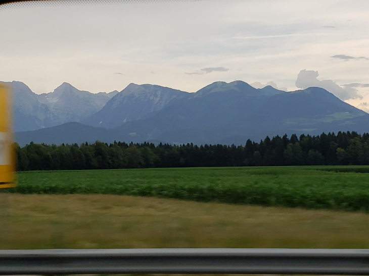 view from a van window of yellow grass, then a green crop, beyond that dark green evergreen trees, and in the distance sort of grayed-out you can see mountains that are a mix of tan and dark green, but like there is a film on it making everything a little grey.