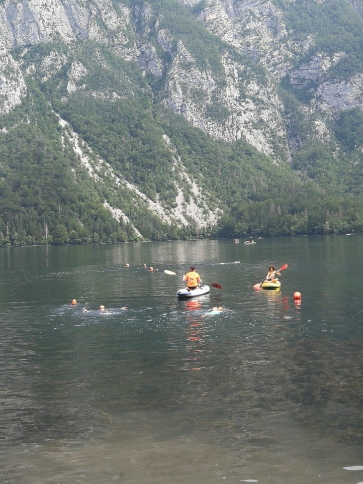 two kayakers with a few swimmers in a lake with a mountain
