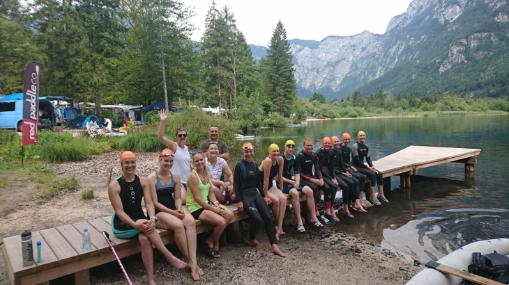 The swim crew decked out in swimsuits and wetsuits sitting on a small wooden dock in lake. Trees and mountain in background