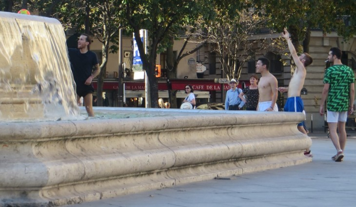 Man dressed in black in the fountain to get his orange and yellow soccer ball. His friends and random people in the square look on.