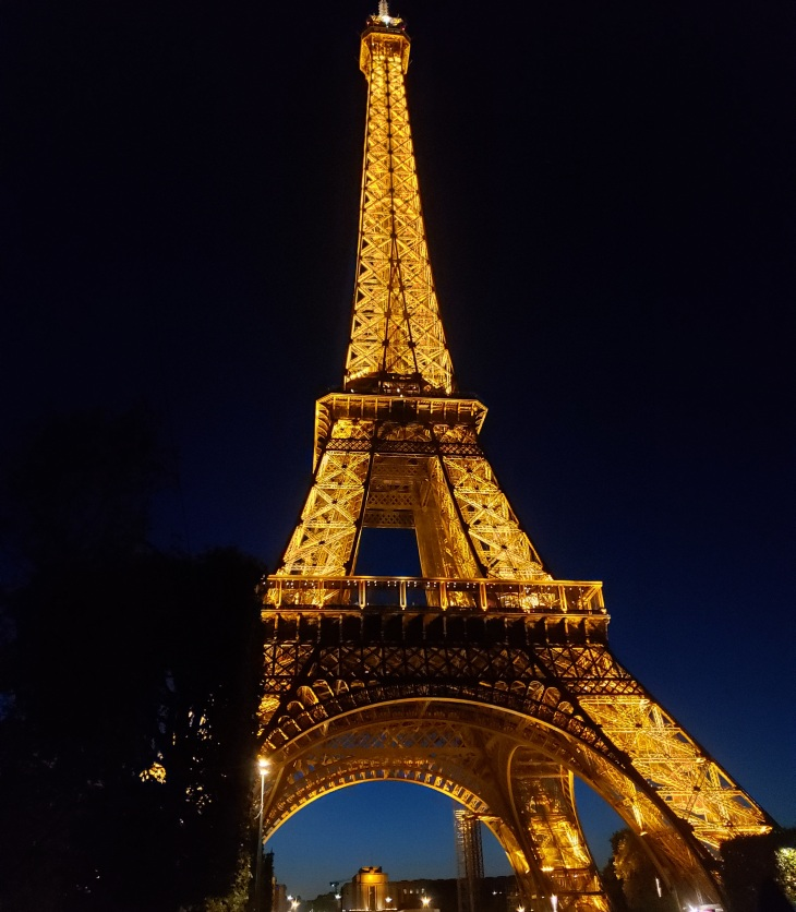 Eiffel Tower at night. Light up with a golden light, black sky in the background