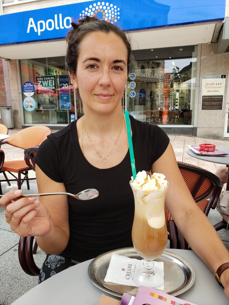 Kerry is wearing a black shirt and is seated at a table with a tall hurricane style glass filled with coffee and ice cream. She is holing a spoon ready to dive into her treat.