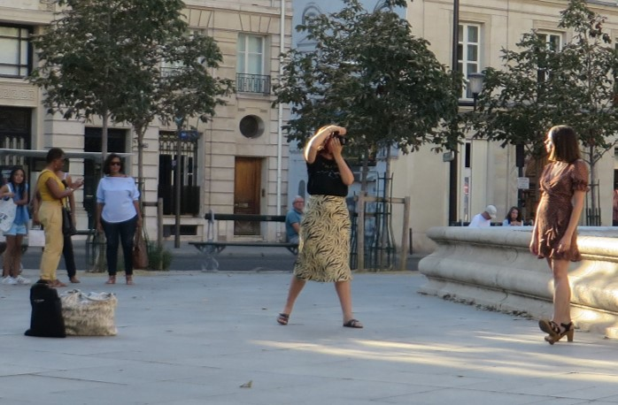 Girl modeling with a small group of people watching her and the photographer