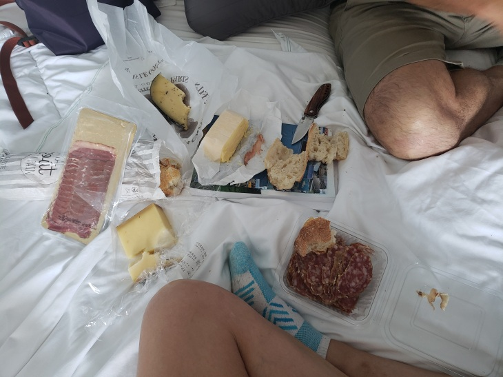 little smorgasbord of cheeses, meats, butter, and bread spread out on our bed with my knee on the bottom of the photo and Patrick's kneed on the top right corner.