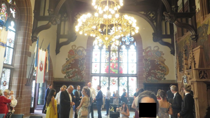 Picture of the inside of the Rathaus where the marriage took place. We see people standing in the room. There is an ornate gold metal 2 tier chandelier. The walls are white with exposed wood and stained glass windows.