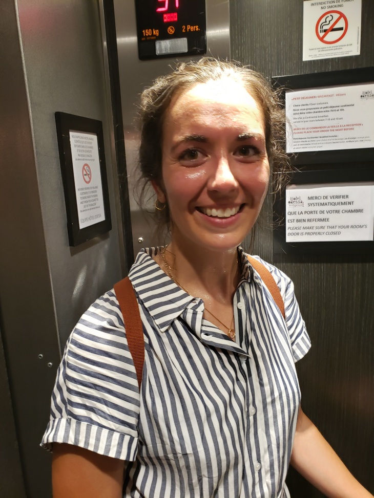 Me in the elevator covered in sweat. Wearing a blue and white striped button down shirt dress and my trusty backpack.