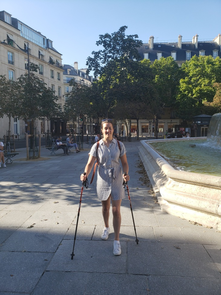 Kerry in a blue and white striped dress, walking with hiking poles in a Paris park square.