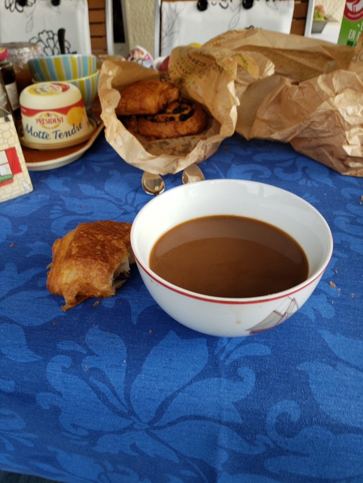 Table with a blue tablecloth. A white bowl filled with coffee, and a half eaten chocolate croissant to the left. In the background is a bag of breakfast pastries and a bucket of butter.