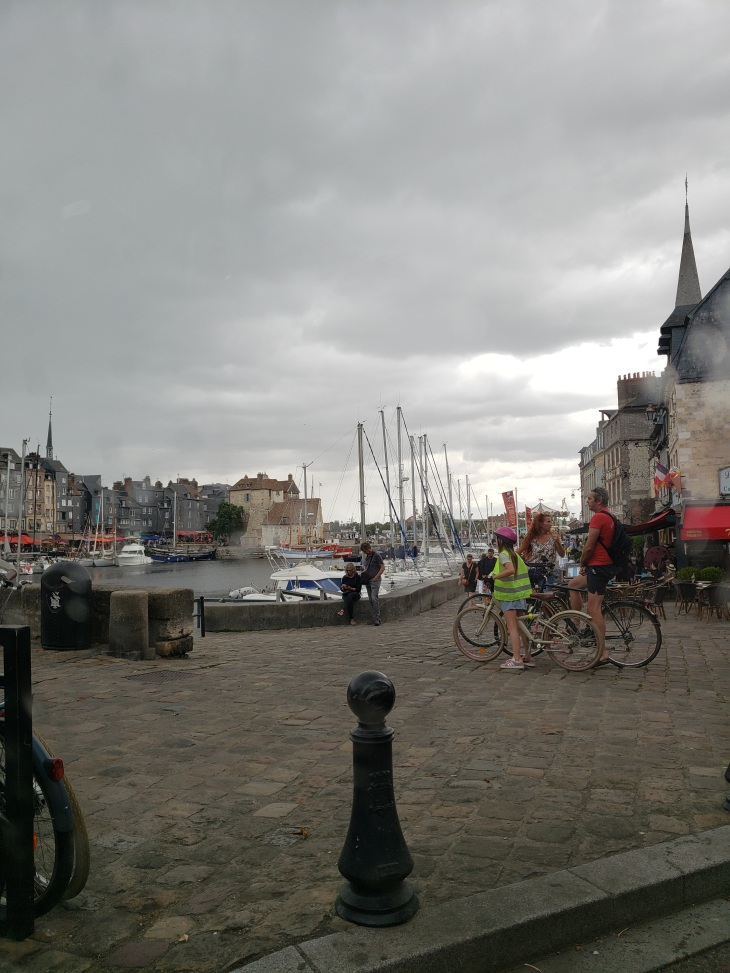 photo of a port, grey skies with houses and sailboats, people on bikes on the sidewalk