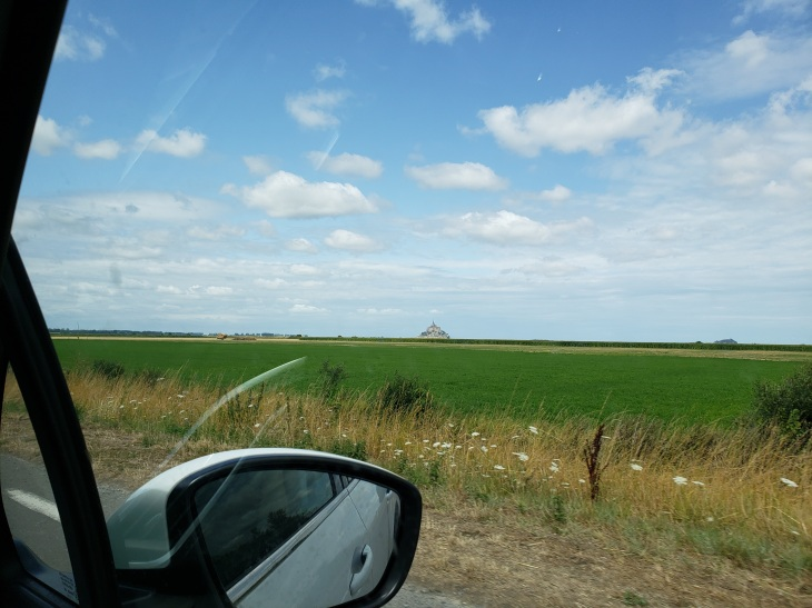 Foreground is the side mirror of the car we were in. Then green fields, clear blue skies with puffs of clouds, and a blob in the middle which is the Mont St. Michel.
