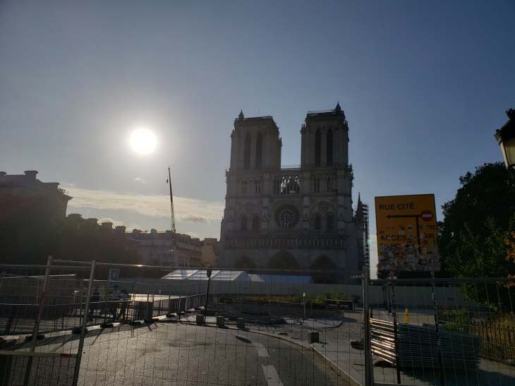 Notre Dame in the background thanks to a construction fence blocking access. The sun is to the left of the Notre Dame