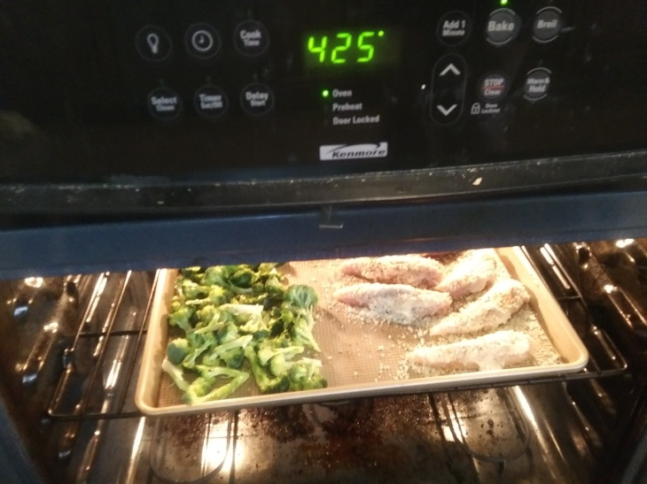 Oven set to 425 degrees, inside there is a sheet pan with broccoli florets on the left, and chicken tenders on the right.