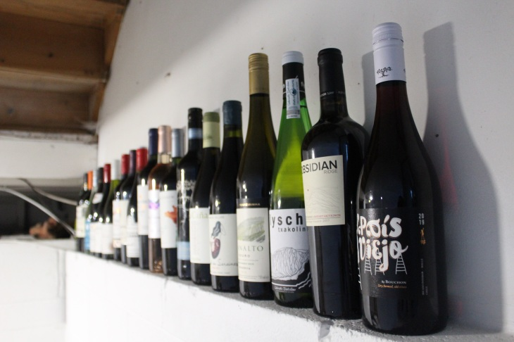 line up of unopened wine bottles on a white wall.