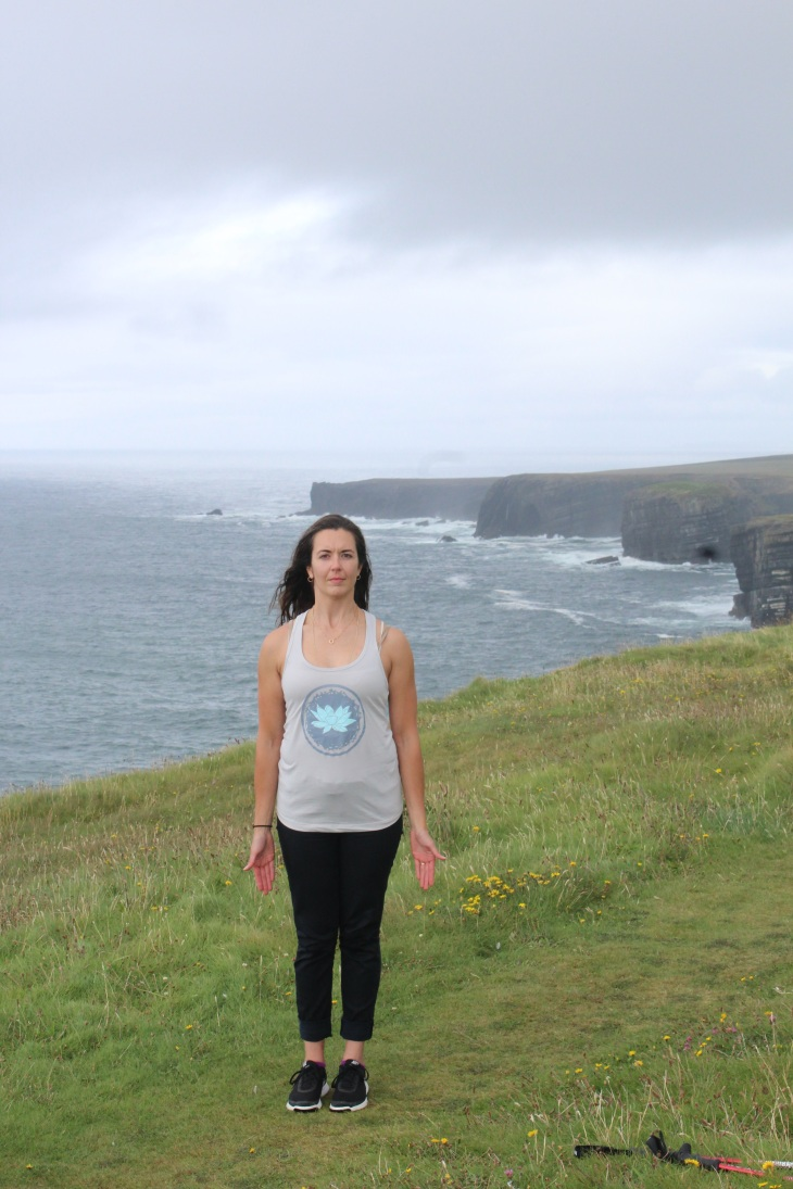 Kerry wearing black jeans, black sneakers, and a grey tank top standing on a grassy field overlooking the ocean with cliffs in the background.
