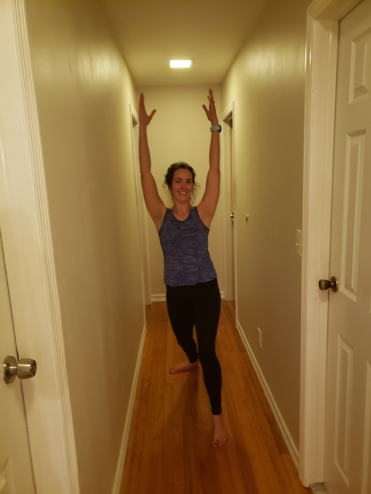 Kerry standing in the middle of her hallway with hands up in the air with her left foot forward in a lunge, warrior one position. She is wearing black leggings and a grown tank top.