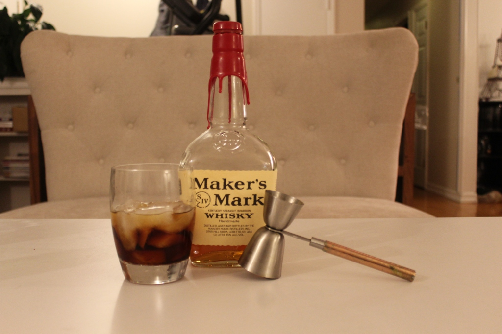 Double old fashioned glass with Punt e Mes and whiskey in it, bottle of Maker's Mark whiskey, and jigger with a handle.