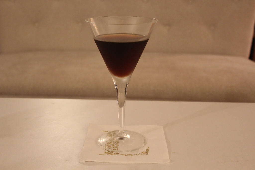Reverse Manhattan in a martini glass on a white cocktail napkin with a gold L.