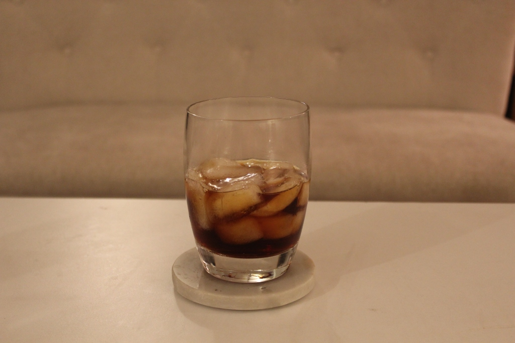 Double old fashioned glass filled with the reverse Manhattan, resting on a grey white marble coaster.