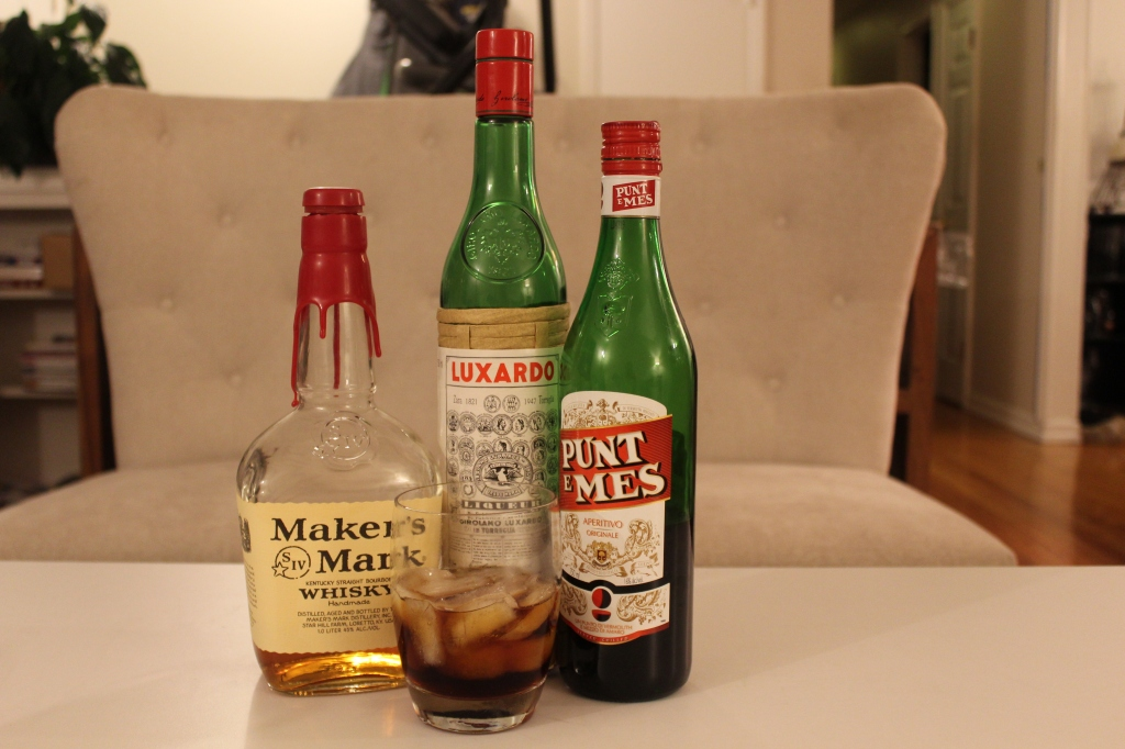picture of a bottle of Manhattan, Luxardo, and Punt e Mes with a double old fashion glass filled with a reverse Manhattan.
