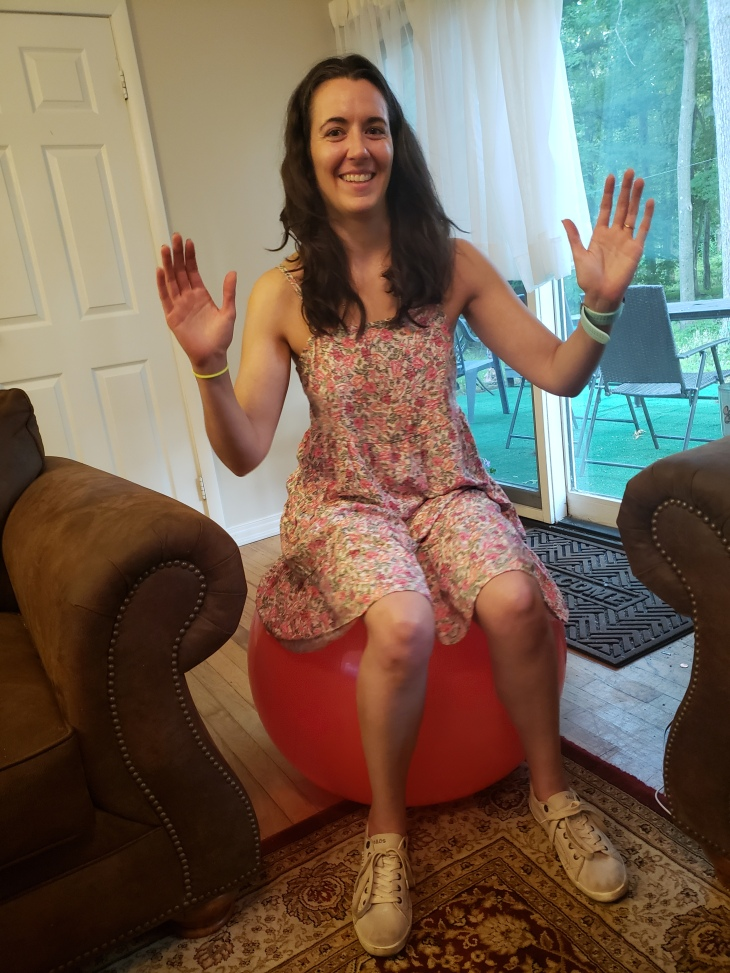 Kerry is wearing a pink floral camisole dress sitting on a red balance ball with sturdy brown couch and chair on either side of her.