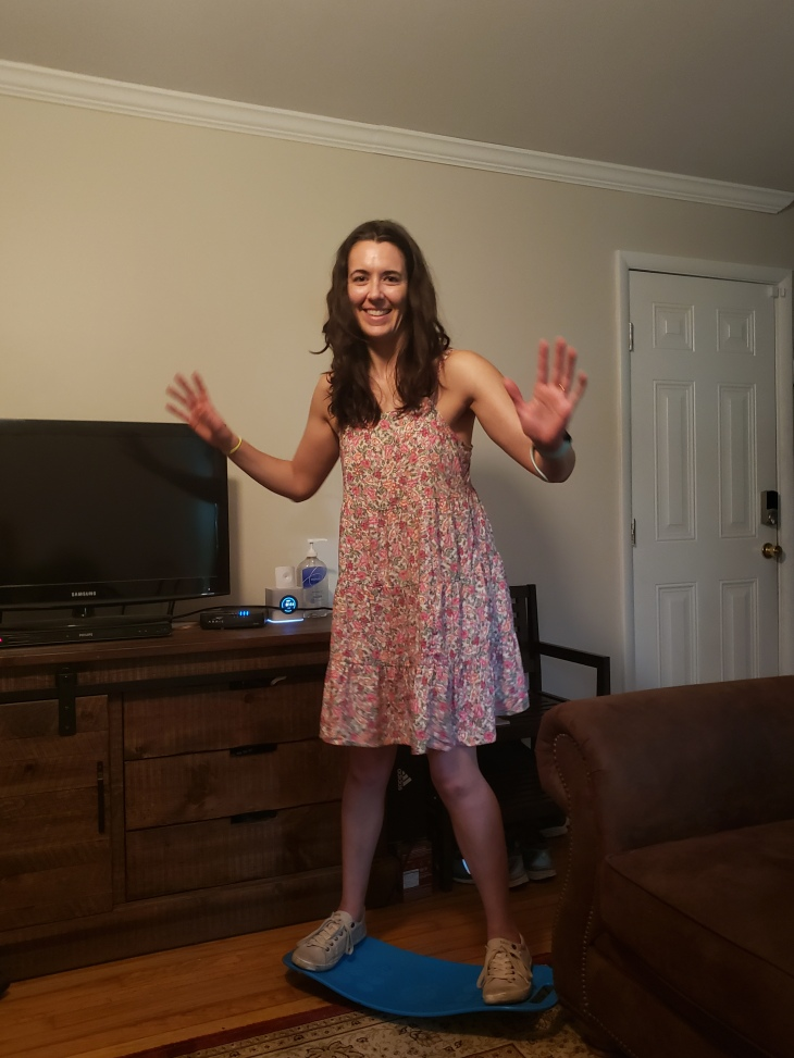 Kerry in pink floral camisole dress standing on a blue Simply Fit Board.  Brown chair is in front of her and the TV console is behind her.