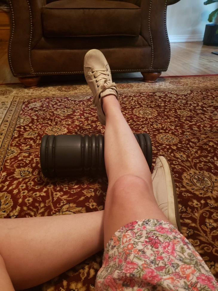 """Kerry's right foot is propped up on a black """"roller"""" so she can do ankle exercises.  Couch is in the background and it all is happening on a red and beige carpet."""